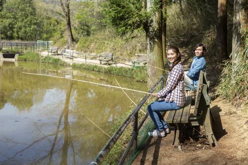 男性 女性 釣り堀 ベンチ 釣り竿 写真