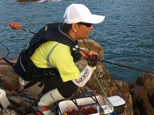 釣り人 男性 マキエサ タモ 海 写真