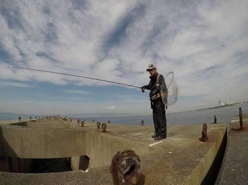 釣り人 男性 釣り竿 タモ スリット 空 写真