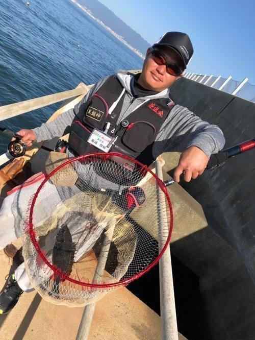 釣り人 男性 クロダイ タモ リール 手すり 海 青空 写真