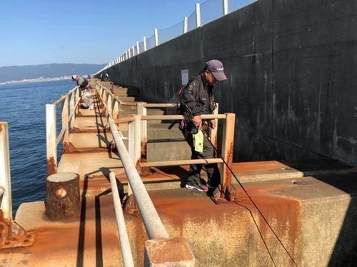 スリット 手すり 釣り人 男性 釣り竿 海 写真