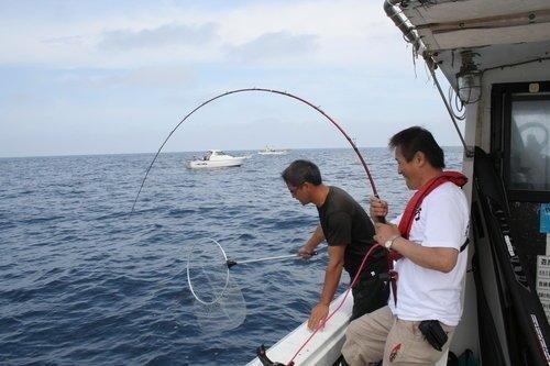 釣り人 男性 釣り竿 タモ 釣船 海 空 写真