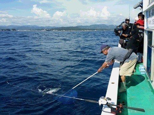 釣り人 男性 タモ 釣り竿 釣船 海 青空 写真