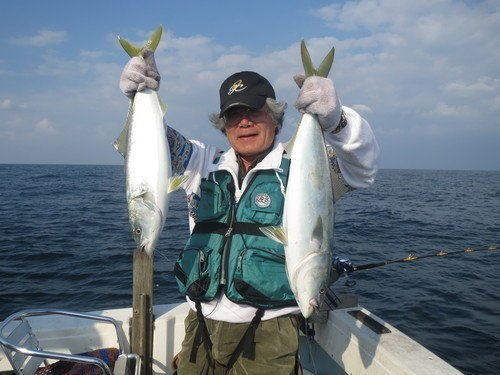 釣り船の上でヒラマサを持つ男性の写真