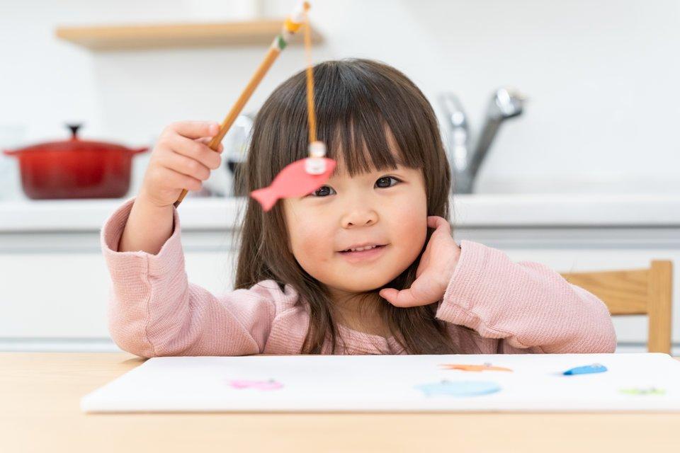 子供 女の子 魚釣りのおもちゃ 机 椅子 台所 写真