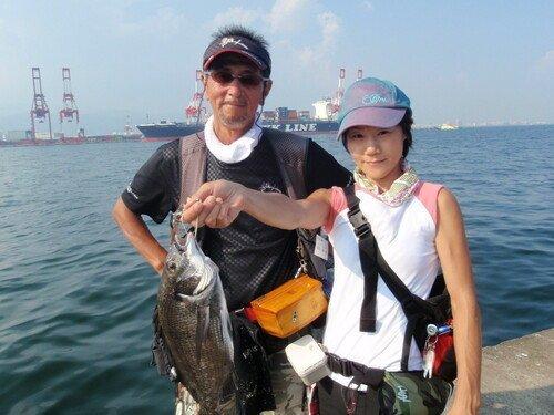 釣り人 男性 女性 クロダイ 海 空 貨物船 写真