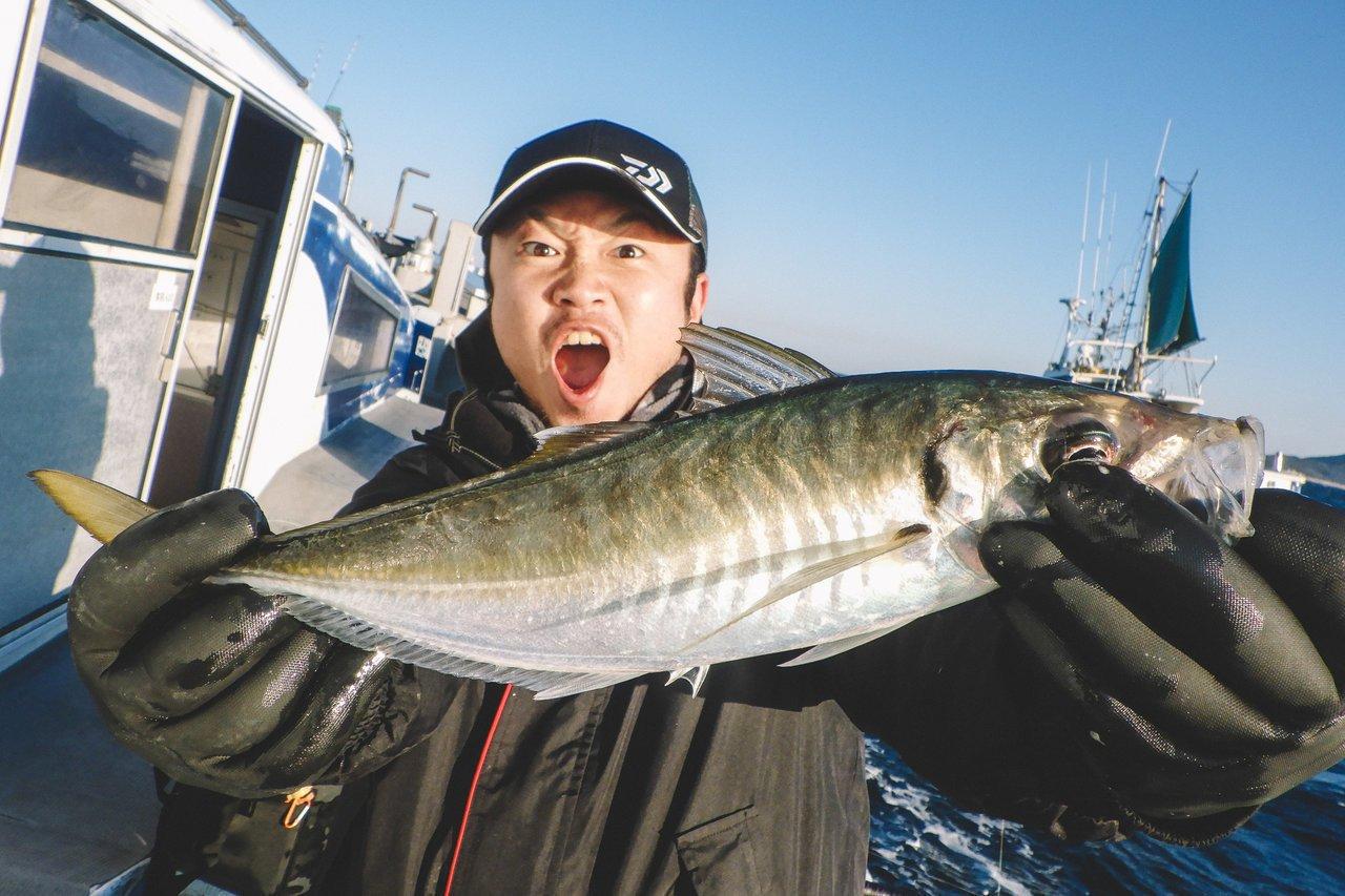大型アジを抱える釣り人の写真