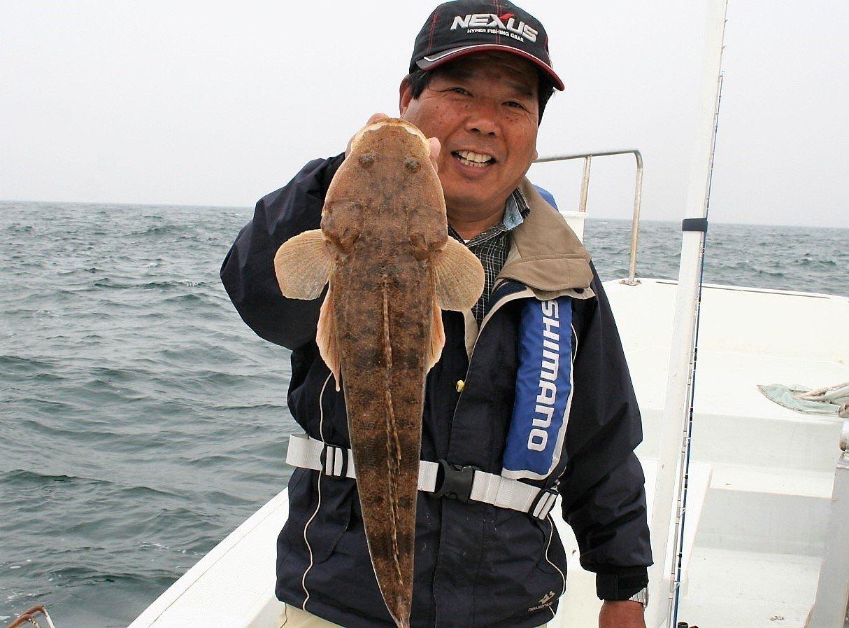 マゴチを釣り上げた男性の写真