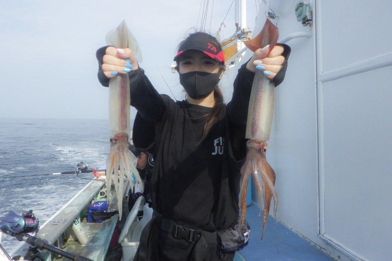 スルメイカと釣り人の写真