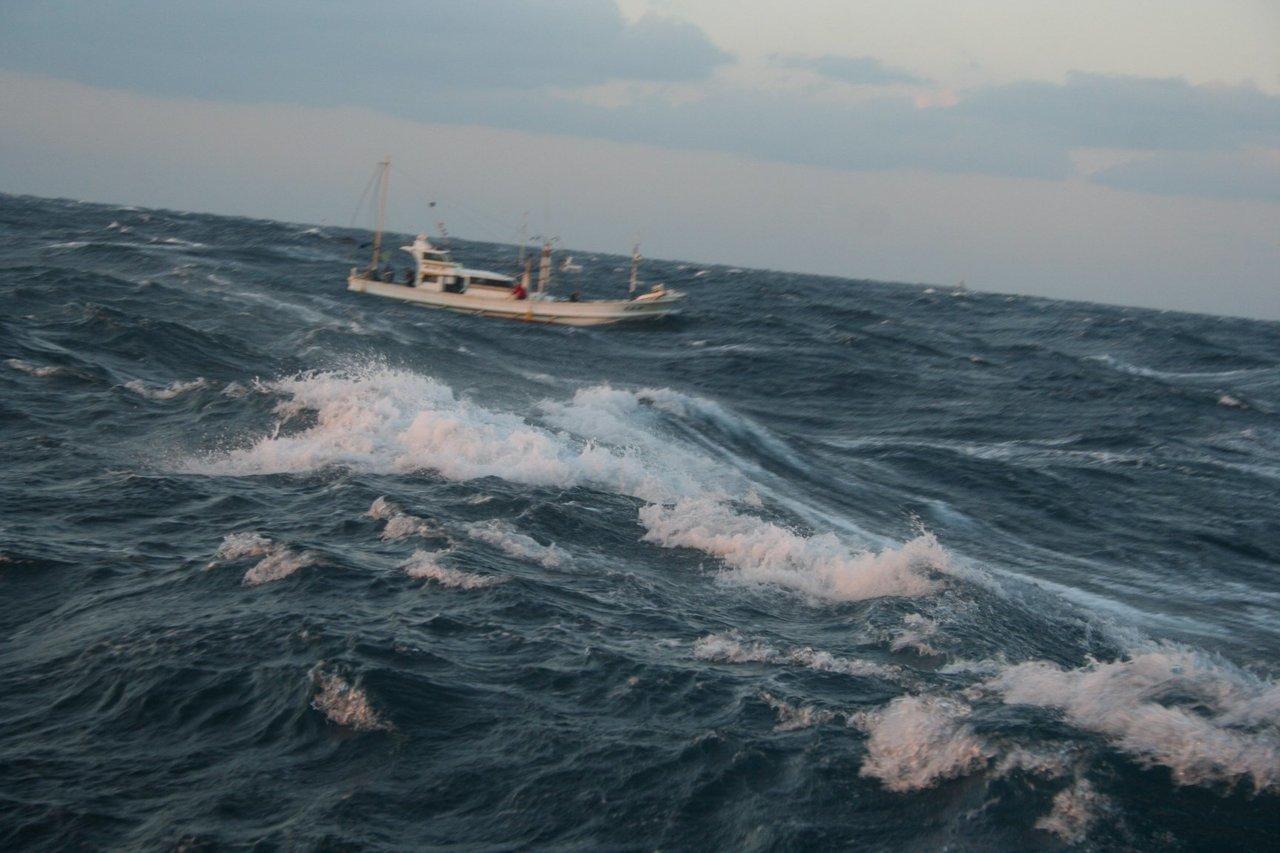 荒れた海と釣り船の写真